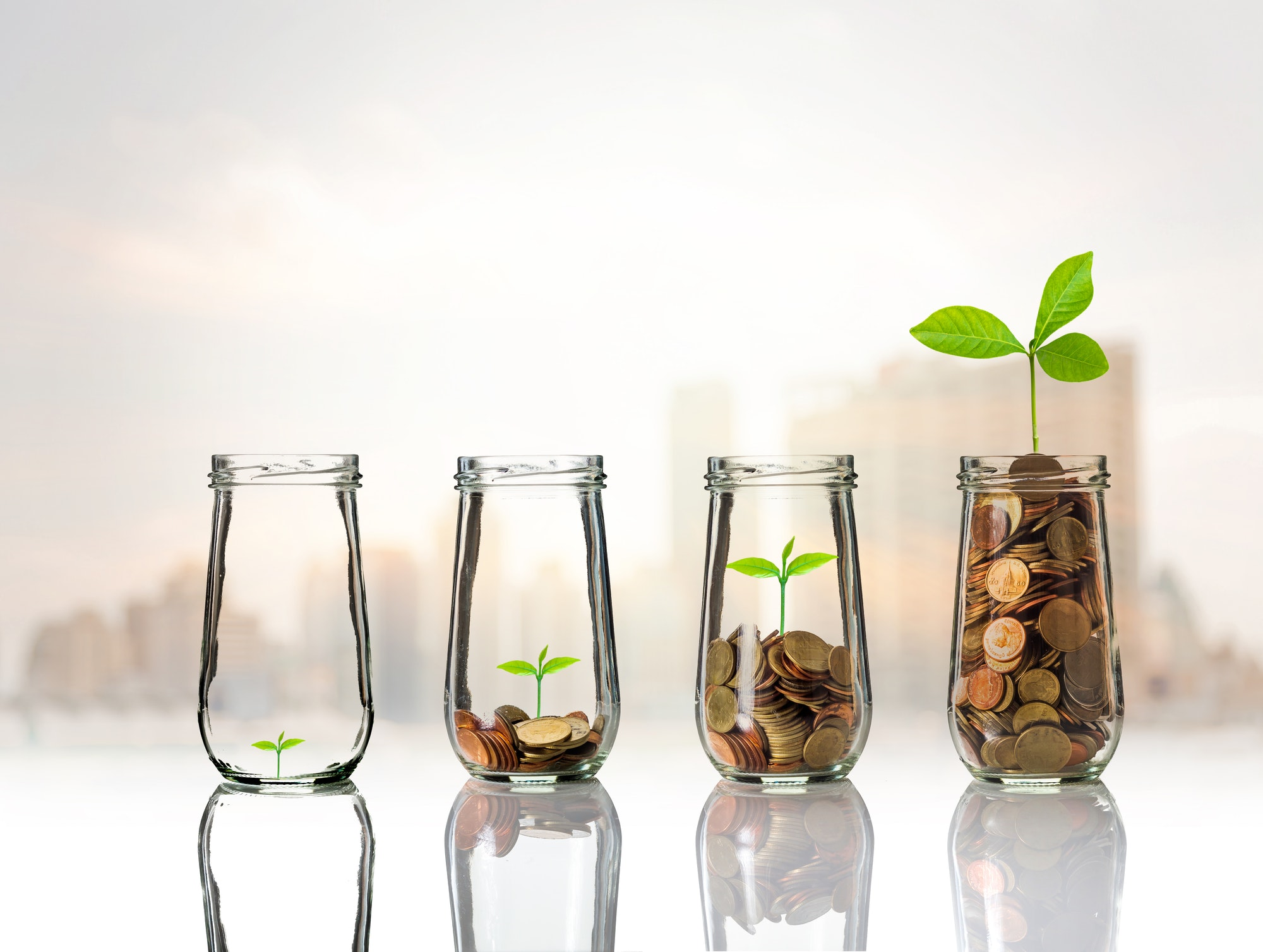 Gold coins and seed in clear bottle on cityscape photo blurred cityscape background