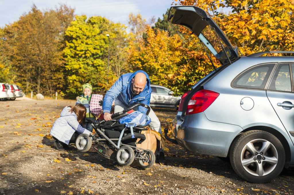 Mature man loading baby carriage in car during family trip